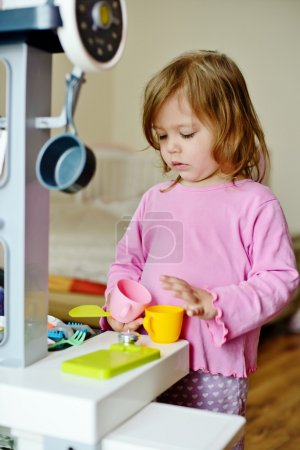 Photo for Toddler girl playing with kitchen at home - Royalty Free Image