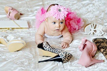 Photo pour Mode bébé fille couché sur le lit avec des chaussures à talons hauts et sac - image libre de droit