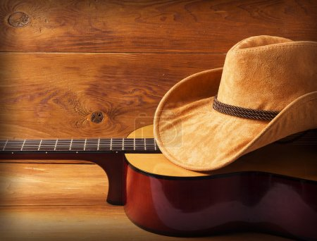 Photo for Guitar and cowboy hat on wood background for text or design - Royalty Free Image