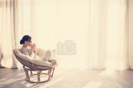 Foto de Young woman at home sitting on modern chair in front of window relaxing in her lliving room reading book and drinking coffee or tea - Imagen libre de derechos