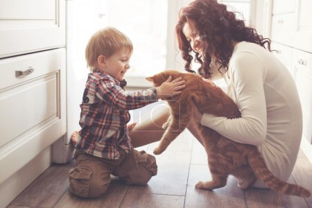 Photo for Mother with her baby playing with pet on the floor at the kitchen at home - Royalty Free Image