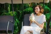 Žena pije čerstvý kokos