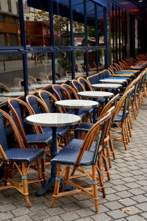 Street Cafe with empty tables and chairs on street in Paris, Fra