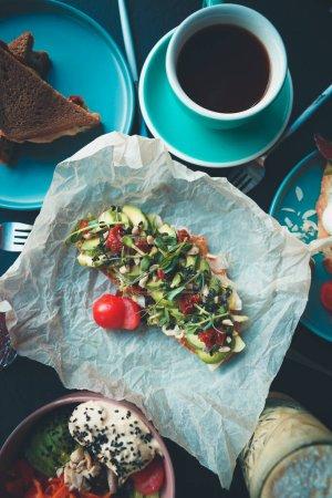 Photo pour Petit déjeuner végétarien sain servi sur la table dans un café végétalien. Délicieux pain grillé à l'avocat préparé avec des avocats tranchés, des tomates séchées, des micro-verts sur du pain bruschetta. Sandwich savoureux aux légumes frais - image libre de droit