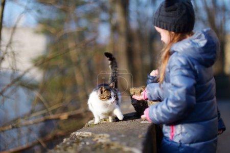 Cute little girl met a cat outdoors