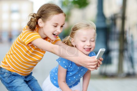 sisters playing on smart phone