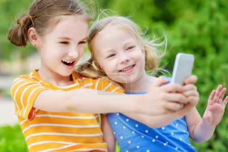 sisters playing outdoor mobile game