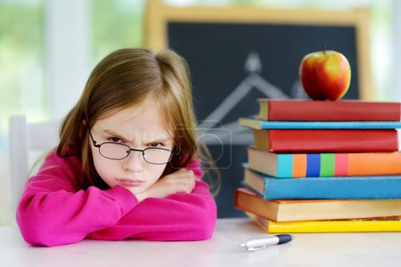Photo for Angry and tired schoolgirl studying with a pile of books on her desk. Child feeling unhappy about going back to school. - Royalty Free Image