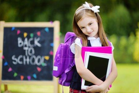 Photo pour Adorable petite fille se sentant très excitée à l'idée de retourner à l'école - image libre de droit