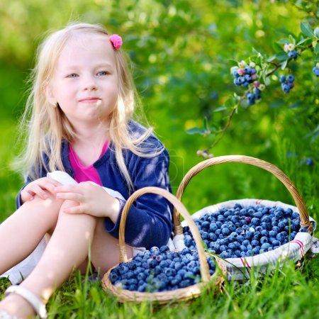 Cute little girl picking berries