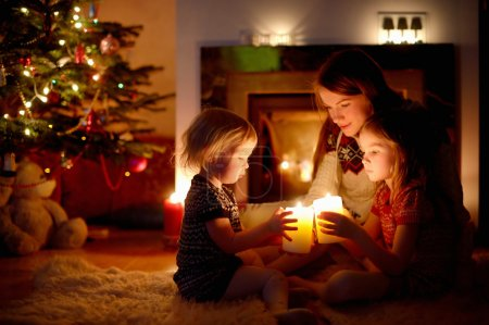 Mother and daughters near fireplace