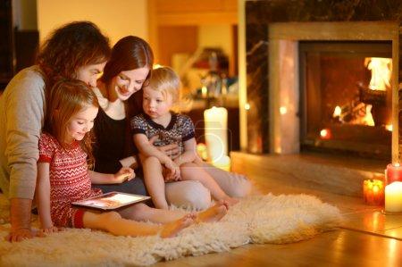 Foto de Familia joven feliz usando un tablet pc en el hogar de una chimenea en salón cálido y acogedor - Imagen libre de derechos