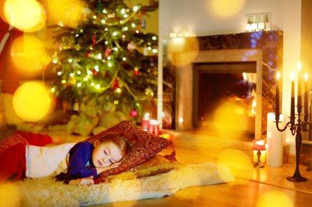 Photo pour Adorable petite fille dormant sous le sapin de Noël près de la cheminée la veille de Noël - image libre de droit