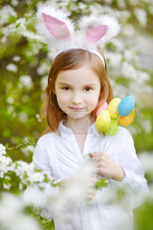 Photo for Adorable little girl wearing bunny ears in spring garden on Easter day - Royalty Free Image