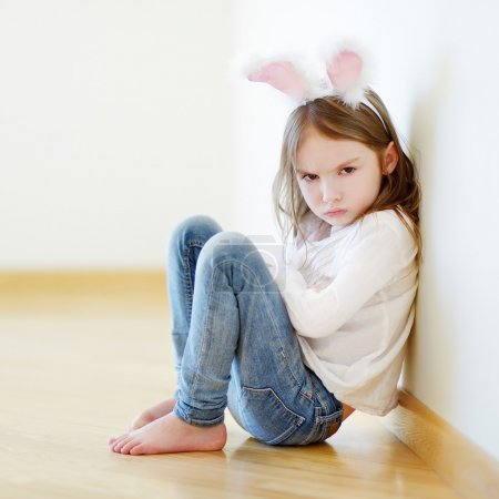 Photo pour Très en colère petite fille portant des oreilles de lapin assis sur un sol à la maison - image libre de droit