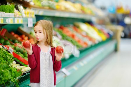 Photo for Little girl choosing tomatoes in market - Royalty Free Image
