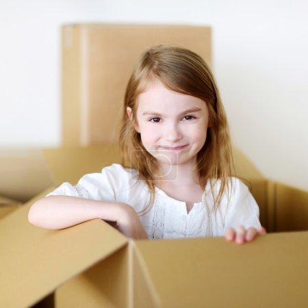 Photo pour Joyeux petit enfant d'âge préscolaire s'amuser à jouer avec une boîte à cartes tout en se déplaçant dans sa nouvelle maison - image libre de droit