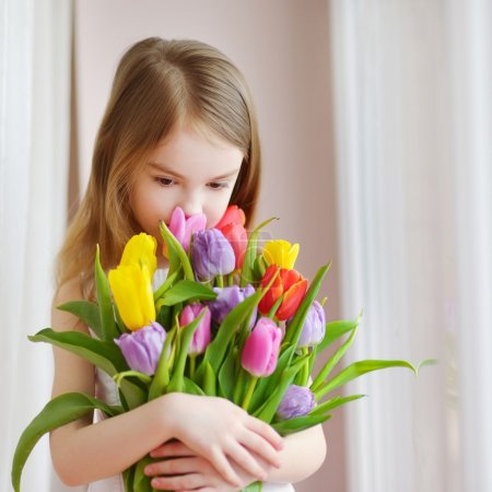 little girl with colorful tulips