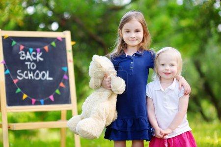 Photo pour Deux adorables petites soeurs, se sentant très enthousiastes de la rentrée scolaire - image libre de droit