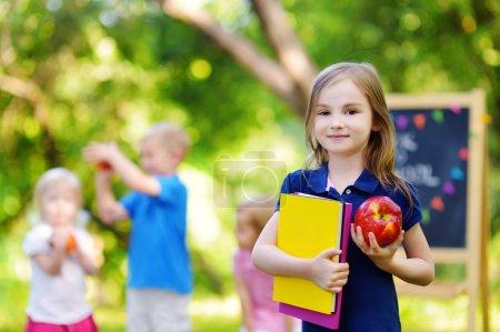 Photo pour Adorable petite écolière se sentant extrêmement enthousiastes de la rentrée scolaire - image libre de droit