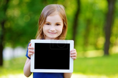 Photo for Happy little girl holding tablet PC outdoors in summer park on beautiful sunny day - Royalty Free Image