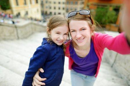 Photo pour Jeune mère et sa petite fille se photographient sur les marches espagnoles à Rome - image libre de droit