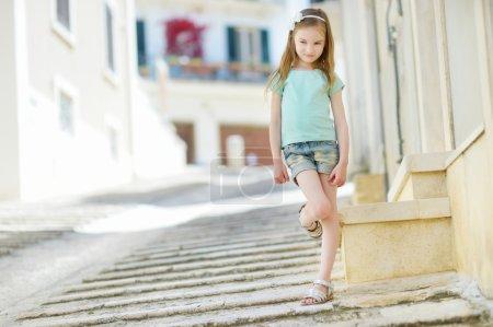 Photo pour Adorable petite fille sur chaude et ensoleillée journée d'été dans la ville italienne typique - image libre de droit