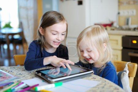 Photo pour Deux adorables petites soeurs jouant avec une tablette numérique à la maison - image libre de droit