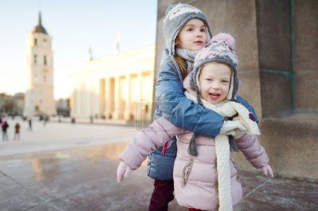 Photo pour Deux adorables petites sœurs amusantes ensemble en hiver Vilnius - image libre de droit