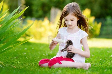 girl feeding small kitten with milk