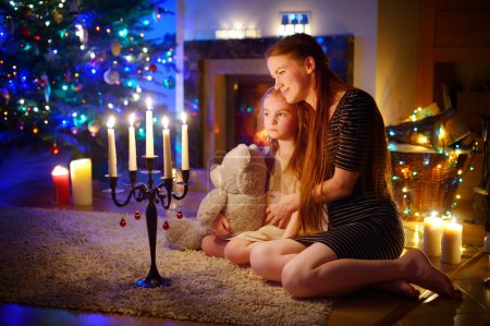 Mother and daughter near fireplace