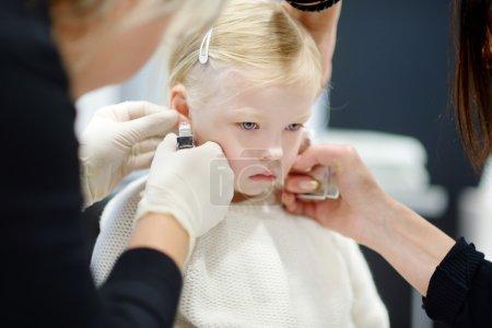 girl having her ears pierced