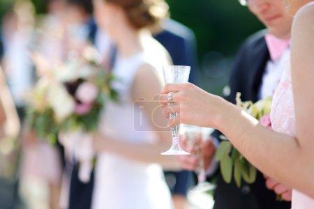 Photo pour Femme tenant une coupe de champagne lors d'un événement festif, une fête ou une réception de mariage - image libre de droit