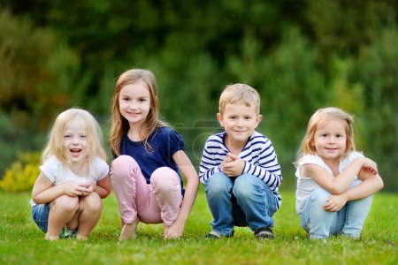 Photo for Four adorable little kids outdoors at warm summer day - Royalty Free Image