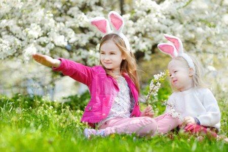 Photo pour Deux adorables petites sœurs s'amusent dans le jardin fleuri du printemps le jour de Pâques - image libre de droit