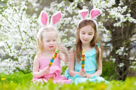 Photo for Two adorable little sisters wearing bunny ears eating colorful gum candies on a stick in blooming cherry garden on Easter day - Royalty Free Image