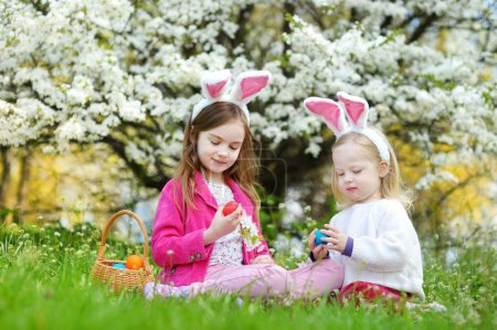 Photo for Two adorable little sisters playing with Easter eggs in blooming spring garden on Easter day - Royalty Free Image
