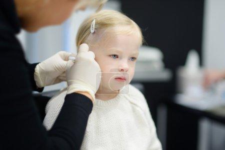 little girl having ear piercing