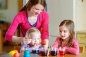 Mother and  daughters painting  Easter eggs