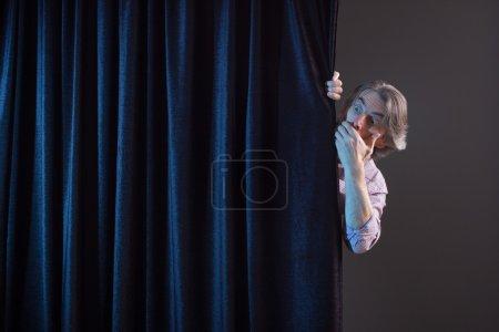 Photo pour Homme peur qui se cache derrière un rideau. - image libre de droit