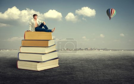 Young man sitting on books