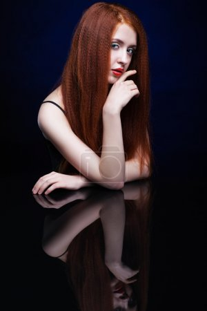 Photo for Beautiful young woman with ginger hair  over reflection mirror on blue background - Royalty Free Image