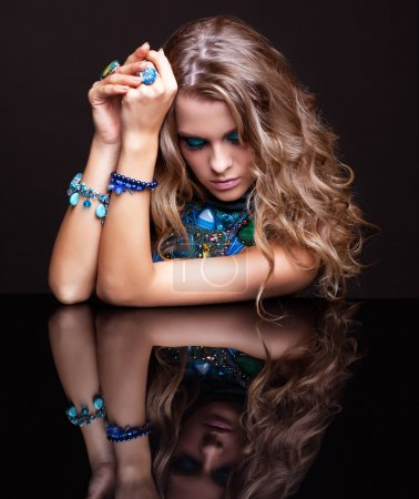 Portrait of young beautiful woman in jewelery at r...