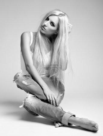 Photo pour Portrait monochrome de jeune femme blonde en jean déchiqueté et gilet assis sur le sol sur fond gris - image libre de droit