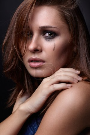 Photo for Young pretty woman with smeared mascara crying on black background - Royalty Free Image