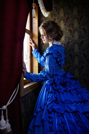 Photo for Young woman in blue vintage dress late 19th century standing near window in coupe of retro railway train - Royalty Free Image