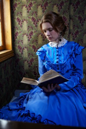 Young woman in blue vintage dress reading the book in coupe of r