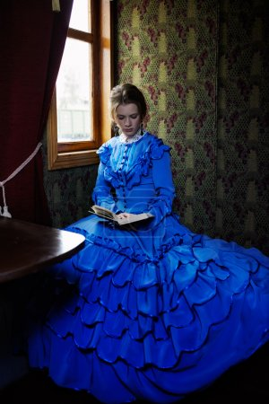 Photo for Young woman in blue vintage dress late 19th century reading the book in coupe of retro train - Royalty Free Image