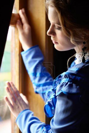 Photo for Young woman in blue vintage dress late 19th century standing near window in coupe of retro railway vehicle - Royalty Free Image