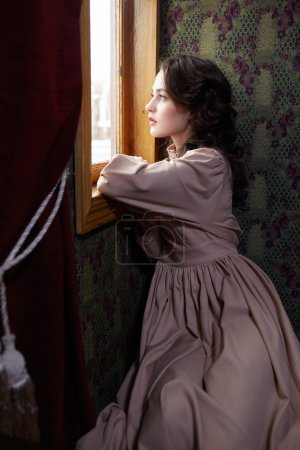 Young woman in beige vintage dress looking trough the  window in